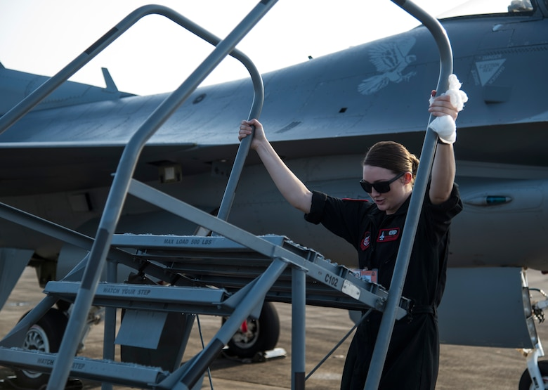 U.S. Air Force Senior Airman Emily Wall, a Pacific Air Forces' Demonstration Team crew chief, moves aircraft steps at Paya Lebar Air Base, Singapore, Feb. 3, 2018. Wall had an opportunity to be one of the few female Airmen who have worked on the team and reinforced international relations between the U.S. and its allies through demo performances. (U.S. Air Force photo by Senior Airman Sadie Colbert)
