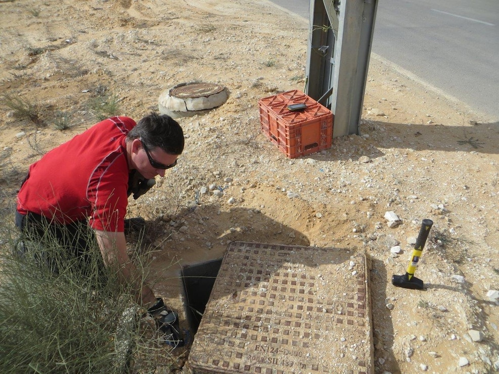 A man crouches on the ground and inspects a manhole cover.