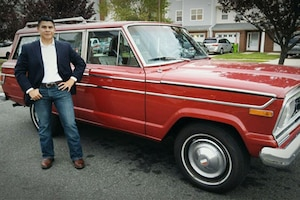 A Marine stands next to a red Jeep Wagoneer.