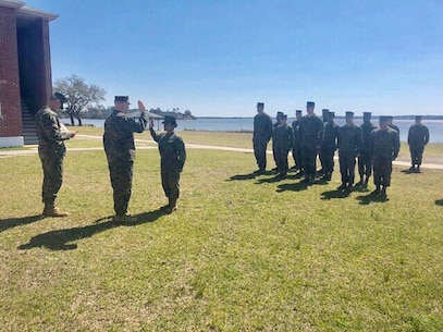 On March 13, 2018 Staff Sergeant Juliette Kemp, an Academic Analyst with Utilities Instruction Company; re-enlists behind BB-13 at Courthouse Bay.  Chief Warrant Officer 5 Micah Butler administers the Oath of Enlistment to SSgt Kemp.