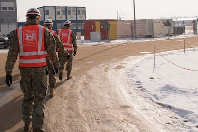 Three men in military uniforms walk along a dirt path on a construction site.