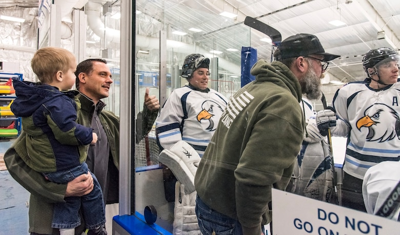 Col. Ethan Griffin, 436th Airlift Wing commander, and his son Paxton, stop by the Dover Eagles bench before the start of a charity hockey game, March 10, 2018, at the Centre Ice Rink in Harrington, Del. The Dover Eagles won the game against the Dover Fraternal Order of Police Lodge 15, 8-4. (U.S. Air Force photo by Roland Balik)
