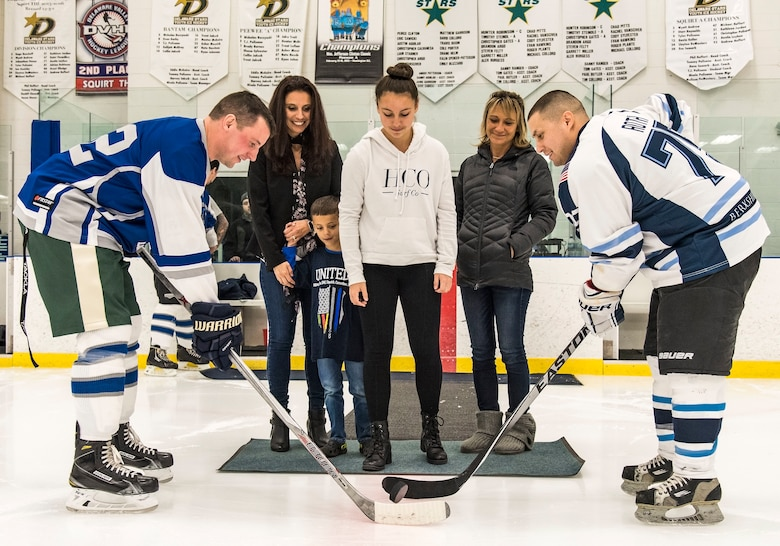 Reilly Hannon, daughter of Dover Police Department officer Cpl. Thomas Hannon, drops the ceremonial first puck to Dover Fraternal Order of Police Lodge 15 forward Christopher Peer (42) and Dover Eagles center Mike Roth (75), March 10, 2018, at the Centre Ice Rink in Harrington, Del. Cpl. Hannon passed away Sept. 1, 2017 as a result of medical complications related to a leg injury he suffered in the line of duty in 2012. (U.S. Air Force photo by Roland Balik)