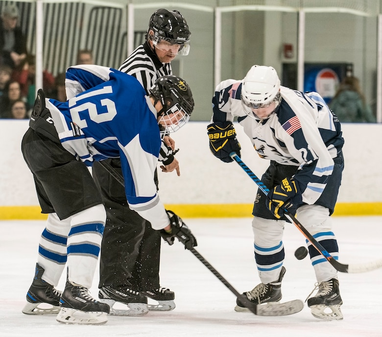 Dover Eagles center Sam Ernst (21), right and Dover Fraternal Order of Police Lodge 15 forward Steven Schultz (12) face off during a charity hockey game March 10, 2018, at the Centre Ice Rink in Harrington, Del. The Dover Eagles hockey team is comprised of current and former members of Team Dover, military retirees and veterans. (U.S. Air Force photo by Roland Balik)