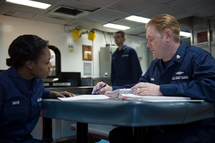 A Coast Guard yeoman assists a fellow Coast Guardsman, Feb. 6, 2013, aboard the Coast Guard Cutter Forward.