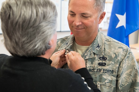 Mrs. Shelia Huffman pins the Air Force retirement lapel pin to Col. Randy C. Huffman's uniform upon the posting of his retirement order March 3, 2018, at McLaughlin Air National Guard Base, Charleston, W.Va. Huffman, the former 130th Airlift Wing Vice Commander, bid farewell to his fellow Airmen and was celebrated for his 37-year career in the Air Force. (U.S. Air National Guard photo by Tech Sgt. Eugene Crist)