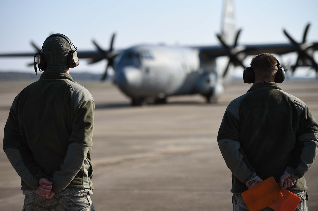 Two Airmen wearing the Airman Battle Uniform and headsets stand with their hands behind their back while looking at a C-130 J.