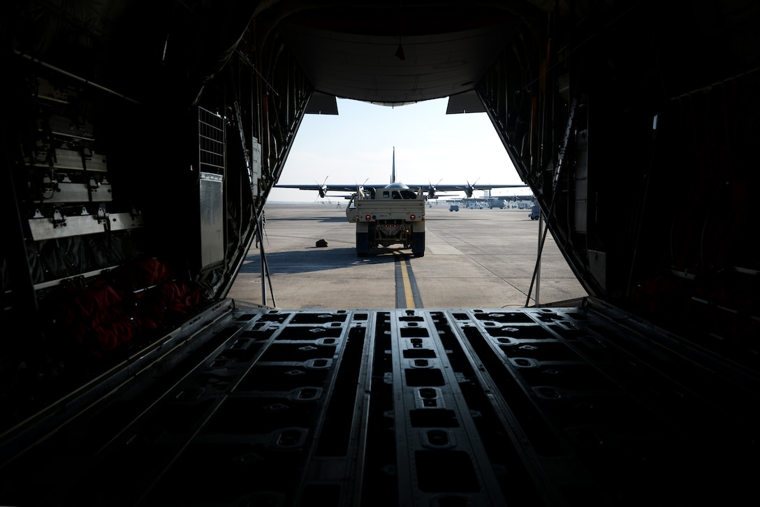 A medium tactical vehicle is see through the back of a C-130 J.