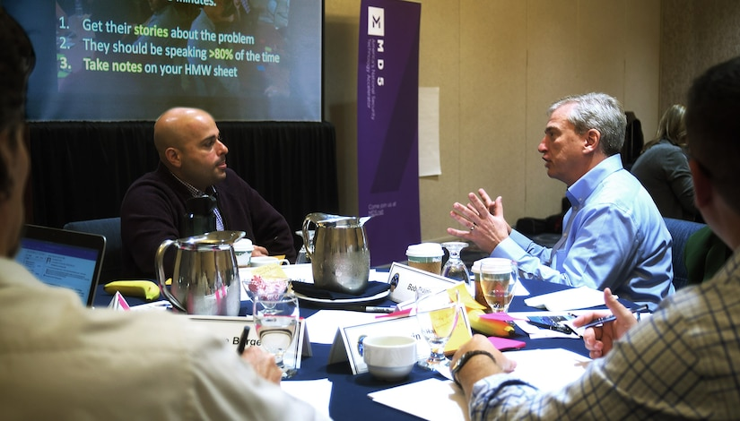 Craig Gravitz, left, of the DLA Information Operations innovation team, discusses a problem statement with Bob Dunlap, director of DLA Cybersecurity Operations, at the DLA Information Operations senior leader innovation boot camp in Springfield, Virginia.