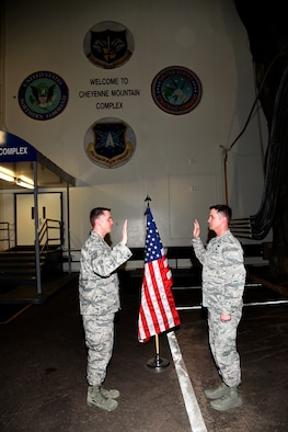 CHEYENNE MOUNTAIN AIR FORCE STATION, Colo. – 1st Lt. Cody Engelke (Right), 18th Space Control Squadron deputy commander of training, reenlists his twin brother Tech. Sgt. Christopher Engelke, 721st Civil Engineer Squadron 1st Air Force regional dispatch center superintendent at Cheyenne Mountain Air Force Station, Mar. 8, 2018. Chris and Cody were born Sept. 1, 1982, the same year that Air Force Space Command opened. (U.S. Air Force photo by Robb Lingley)