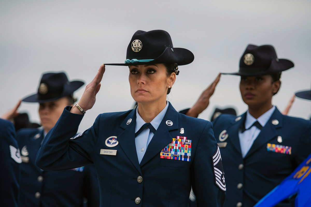 Female military instructors stand in formation and salute.