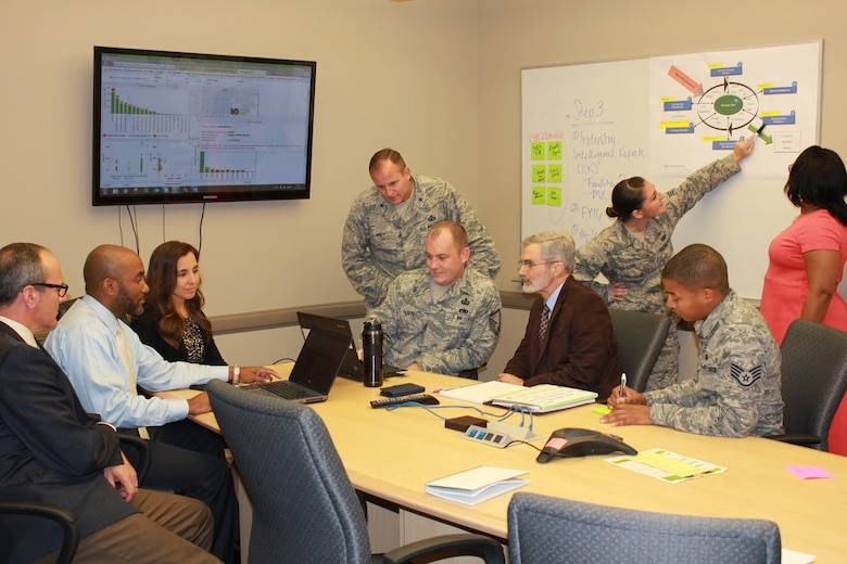 AFICA commander Brig. Gen. Cameron Holt and several members of his team discuss contracting strategies. Using a Cost Savings Tracker, AFICA recently captured more than $1 billion in budgetary savings and cost avoidance. (Courtesy photo)