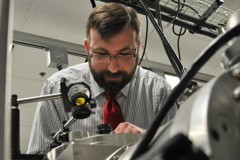 Dr. William Lewis, AFRL Senior Research Chemist with the Turbine Engine Division, Aerospace Systems Directorate, checks the C3 (carbon) evaporation process happening in the Cluster Assembly and Spectroscopy Instrument. (U.S. Air Force Photo/Staff Sgt. Ashley Clingerman)