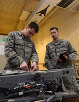 Air Force Airman Joseph Tower and Airman 1st Class Cody Oleson-Massa, both egress technicians with the 28th Maintenance Squadron, inspect an Advanced Concept Ejection Seat from a B-1 Lancer bomber at Ellsworth Air Force Base, S.D.