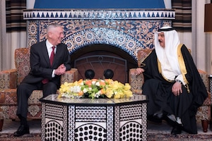 Defense Secretary James N. Mattis and the Bahraini king smile and chat while sitting in armchairs in front of an ornate tiled fireplace.