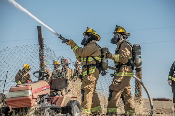 Two firefighters spray water on a structure fire