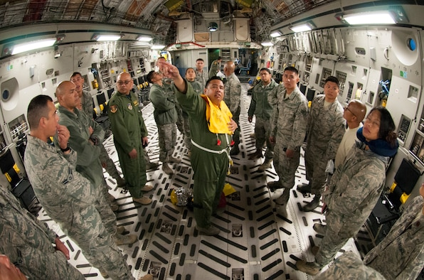 Tech. Sgt. Andrew Vierra Villanueva, center, a load master with the 204th Airlift Squadron conducts a preflight safety briefing on board a C-17 Globemaster to airmen from the 154th Medical Group, Detachment 1, Hawaii Air National Guard,  at Joint Base Pearl Harbor-Hickam, Jan. 26, 2018.