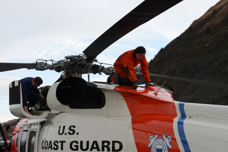 Petty Officer 2nd Class Eileen Best, an aviation maintenance technician, performs post-flight checks on an MH-60 Jayhawk helicopter at Coast Guard Air Station Kodiak, Alaska, Feb. 13, 2018.