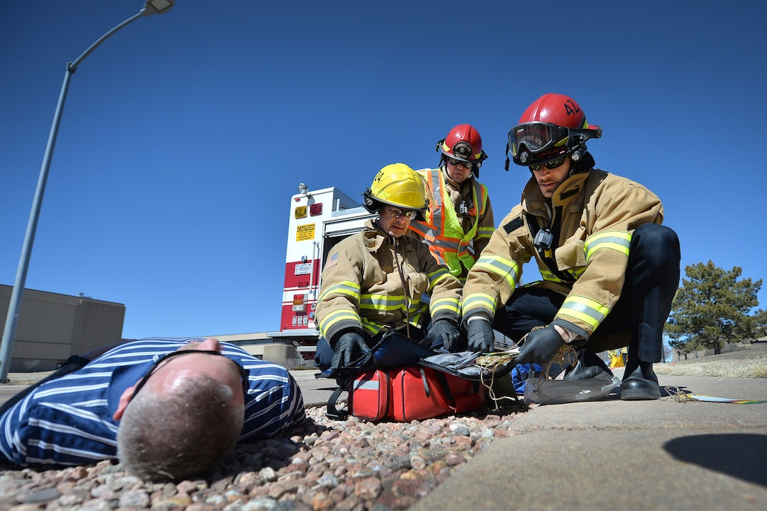 James Kuhn, Jerry Quintana, and Jon Rinesmith, firefighters with the Schriever Air Force Base Fire Department, tend to an exercise victim during Opinicus Vista 18-1 at Schriever Air Force Base, CO, March 6, 2018. The 50th Space Wing Inspector General's office conducted OV 18-1 to evaluate the wing's first responders' ability to respond to an emergency situation. (U.S. Air Force photo by Dennis Rogers)