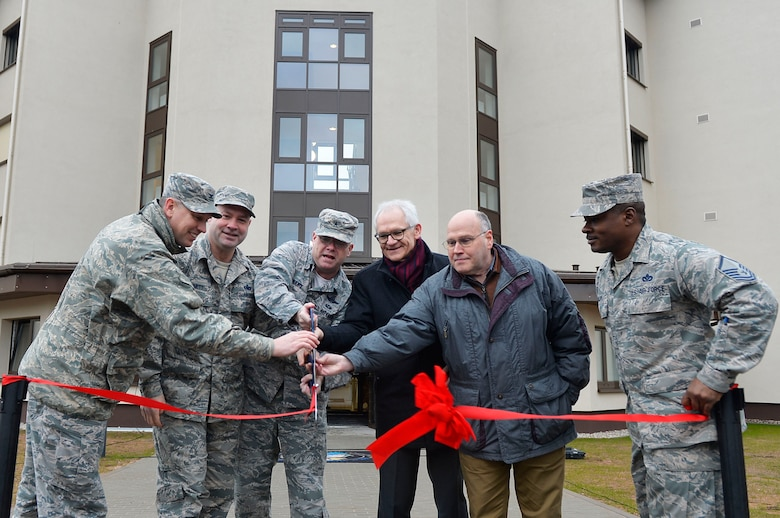 Officials assigned to the 86th Airlift Wing, U.S. Army Corps of Engineers, and the Kaiserslautern State Construction Agency cut a ribbon during a ceremony for a new dormitory building on Ramstein Air Base, Germany, March 7, 2018. The new dorm, 2411, is expected to replace the older dorm 2413. (U.S. Air Force photo by Senior Airman Joshua Magbanua)