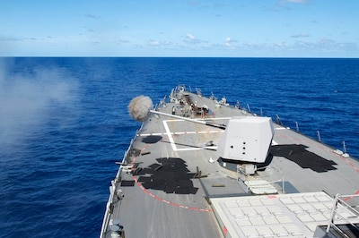 The guided missile destroyer USS Mustin fires its 5-inch gun