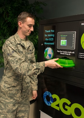 Airman 1st Class Casey Robertson, 366th Force Support Squadron food service apprentice, demonstrates how to use the OZZI drop off machine at Mountain Home Air Force Base, Idaho, March 13, 2018. The new programs goal is to save the earth while saving money. (U.S. Air Force photo by Senior Airman Chester Mientkiewicz)