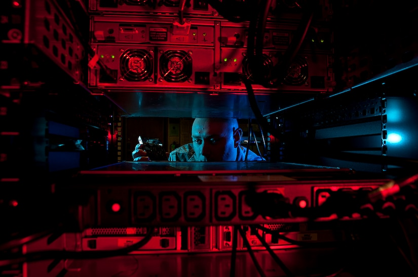 Air Force Staff Sgt. Jerome Duhan, a network administrator with the 97th Communications Squadron, inserts a hard drive into the network control center retina server at Altus Air Force Base, Okla.
