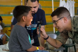 An Air Force doctor looks into a child's mouth during a physical exam in Honduras.