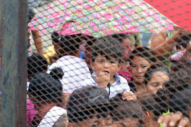 Hondurans wait in line to be seen by a medical team