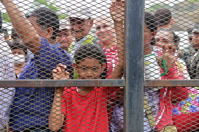 Hondurans wait in line to be seen by medical personnel.