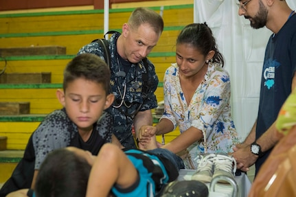 A Navy doctor shows a mother physical therapy exercises in Honduras.