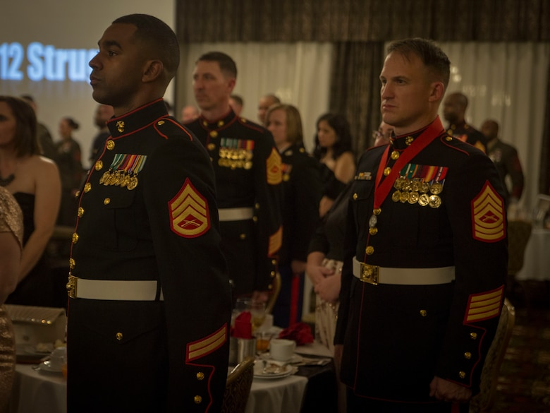 Artillery Marines stands at attention for the Marine Corps Hymn during 3rd Battalion, 12th Marine Regiment's St. Barbara's Day celebration, March 9, 2017. St. Barbara's Day is celebrated by artillery Marines to recognize those who have given a lifetime of servitude to the artillery community.