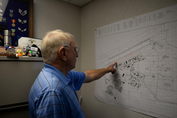 Man wearing a blue striped polo shirt points to a map.