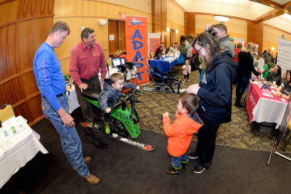 Don Hickman and Jim Bradley, ADAPT sports, demonstrate a ski chair to Sara Clippinger and children during the Special Needs Summit March 15, 2018, at Hill Air Force Base, Utah. The annual summit gives the base community a chance to research and learn about many special needs services and opportunities available in the area. (U.S. Air Force photo by Todd Cromar)