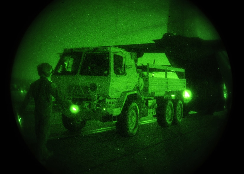 A green night vision photo depicting a vehicle being loaded onto an aircraft.
