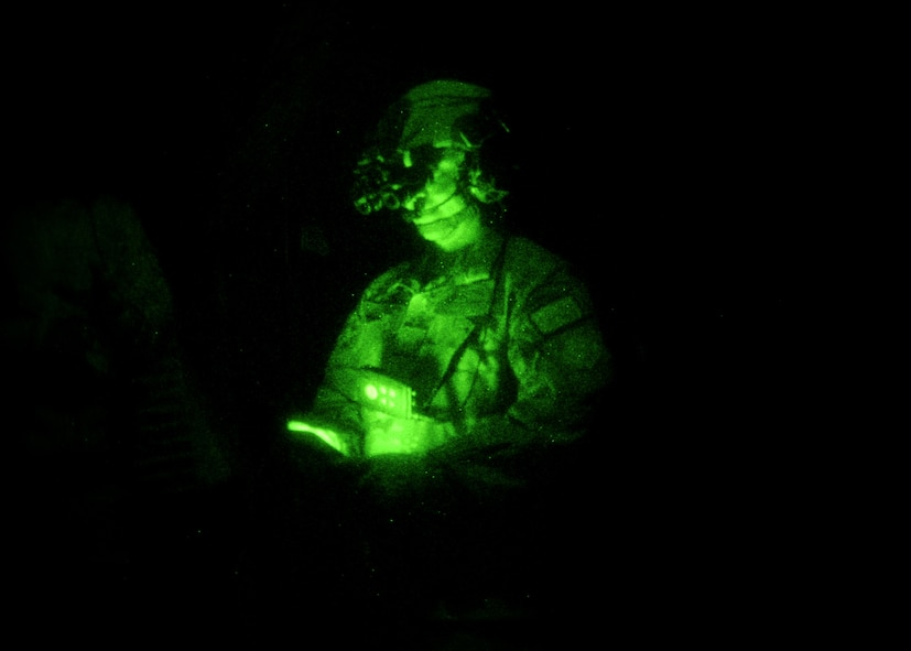 A green night vision photo depicting a male wearing night vision goggles in a completely black aircraft.