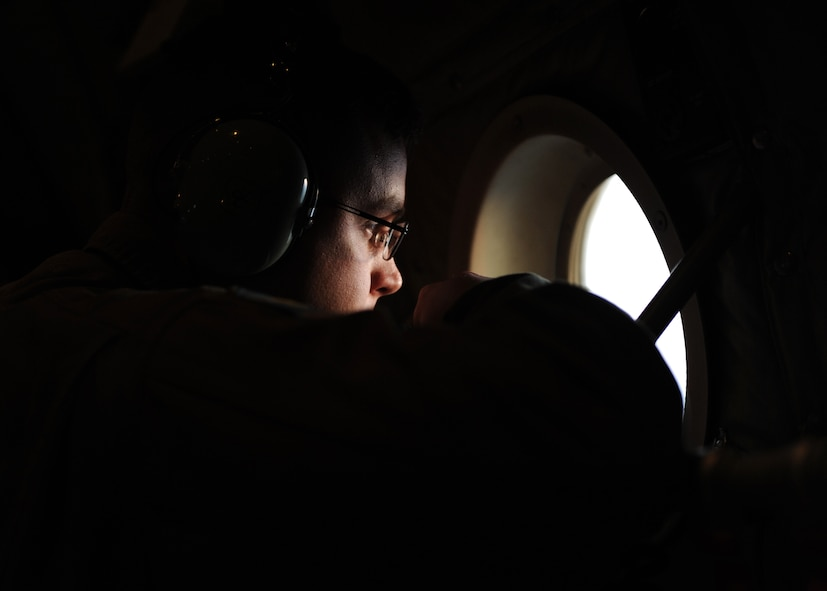 A male in a completely dark aircraft looks out a window with bright light coming from outside.