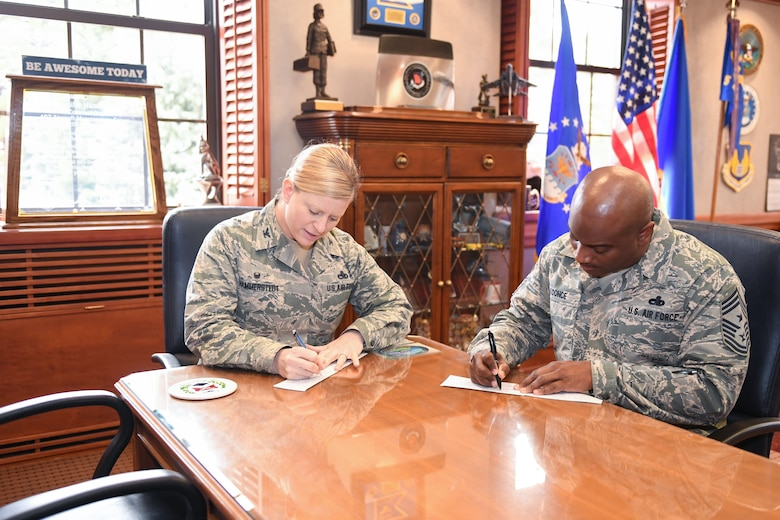 Col. Jennifer Hammerstedt, 75th Air Base Wing commander, and Chief Master Sgt. Rodney Koonce, 75th ABW command chief, sign Air Force Assistance Fund pledge forms to kick off the 2018 AFAF fundraising campaign. The Hill Air Force Base 2018 campaign will run March 26 through May 4. (U.S. Air Force photo by Cynthia Griggs)