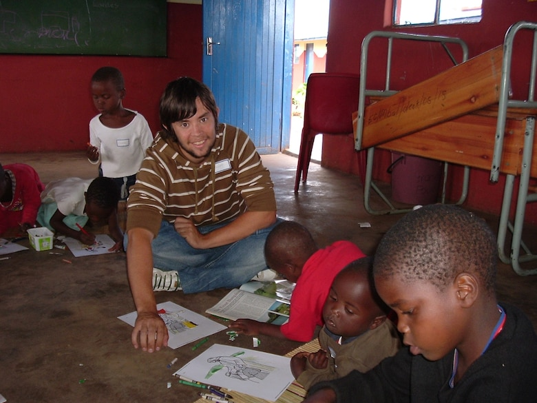 SCHRIEVER AIR FORCE BASE, Colo.—Scott Munro, now a senior airman 50th Civil Engineer Squadron engineering assistant, works with children during a mission trip, Ingwavuma, South Africa, 2008. This mission trip occurred during his year of internship at his church prior to embarking upon an Air Force career.  (Courtesy Photo)
