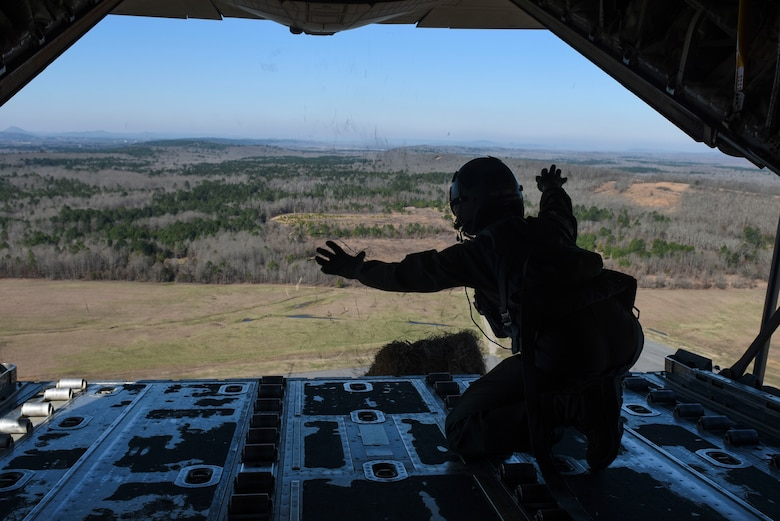 An Airman flies in the back of an aircraft and drops a hay bale during a training event