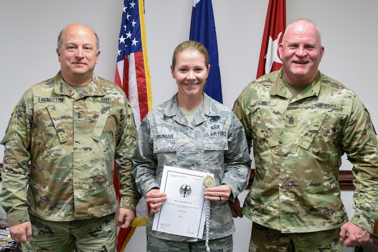 U.S.Army Maj. Gen. Robert E. Livingston Jr., adjutant general for South Carolina and State Command Sgt. Maj. Russel A. Vickery present the Schutzenschnur Badge to Master Sgt. Wendy Broman, a financial management specialist assigned to the South Carolina Air National Guard's 169th Fighter Wing, for demonstrating profeciency in firing German weapons at a ceremony March 7, 2018 at the Adjutant Generals' building in Columbia S.C. Broman and several other service members were chosen to participate in a specialized training opportunity to work with German soldiers. They learned how to fire a German rifle, pistol and machine gun. (U.S. Army National Guard photo by 1st Lt. Tracci Dorgan)