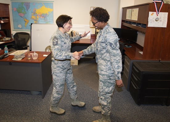 Command Chief Master Sgt. Ericka E. Kelly (left) hands Staff Sgt. Raven Calloway, 412th Logistics Readiness Squadron, an Air Force Reserve Command coin for a job well done March 9. Kelly is the U.S. Air Force Reserve Command's highest ranking enlisted member. Calloway is an Air Force Reserve Airmen on temporary duty from Dobbins Air Reserve Base, Georgia, assigned to the 412th LRS. (U.S. Air Force photo by John Perry)