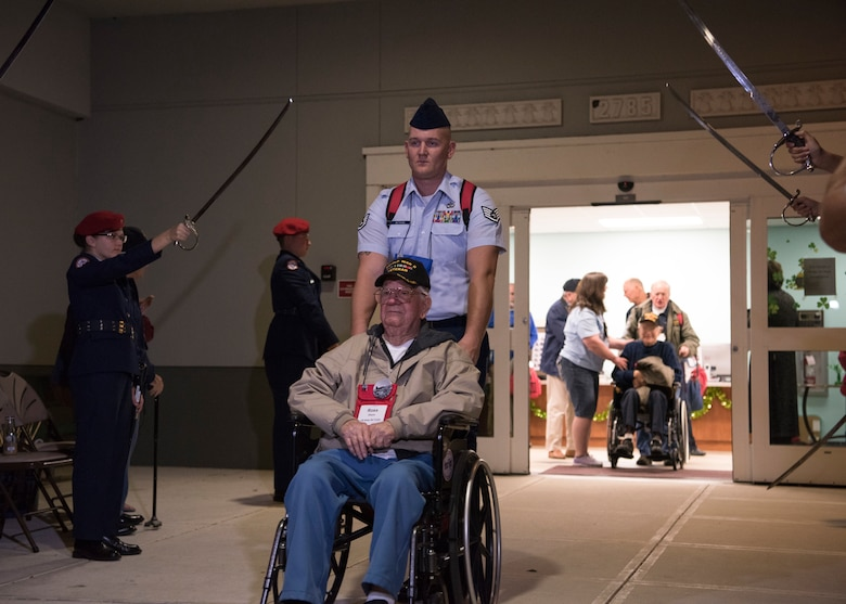 Airmen helps veteran move through a tunnel of sabers, March 17, 2018 at Wickham Park Senior Center in Melbourne, Fla. Honor Flight veterans move through a saber arch before traveling to Washington D.C.