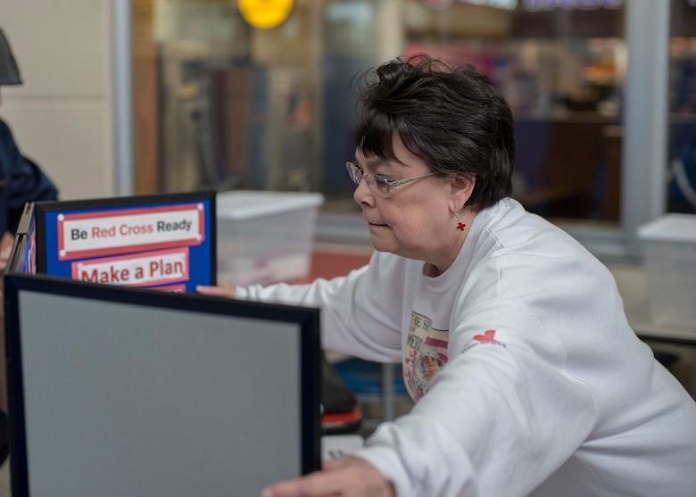 Karen Jorgenson, the American Red Cross of Misawa regional program manager, sets up the build your own emergency disaster kit booth at Misawa Air Base, Japan, March 16, 2018. The annual workshop equips Airmen and their families in light of a natural disaster. (U.S. Air Force photo by Airman 1st Class Collette Brooks)