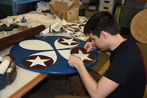 02/28/2018) -- Museum restoration specialist Casey Simmons works on the wheel covers for the Boeing B-17F Memphis Belle. Plans call for the aircraft to be placed on permanent public display in the WWII Gallery here at the National Museum of the U.S. Air Force on May 17, 2018. (U.S. Air Force photo by Ken LaRock)