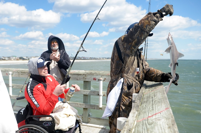 "Georgia Army Cpl. Alika Gitolendia, left, a member of the 2018 Marine Corps Trials Georgian team catches a small shark at Ocean Crest Pier in Oak Island, N.C., March 14, 2018, as part of the USO of North Carolina's ""American Experience Day."" The Marine Corps Trials promotes recovery and rehabilitation through adaptive sport participation and develops camaraderie among recovering service members and veterans. It is as an opportunity for RSMs to demonstrate their achievements and serves as the primary venue to select Marine Corps participants for the DoD Warrior Games."
