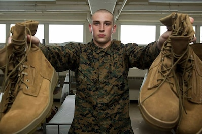 A recruit from Delta Company, 1st Recruit Training Battalion, holds out his boots during pick up at Marine Corps Recruit Depot San Diego, March 9. This is part of an initial gear inspection recruits must go through to ensure they have all the required gear needed for recruit training. Annually, more than 17,000 males recruited from the Western Recruiting Region are trained at MCRD San Diego. Delta Company is scheduled to graduate June 1.  (Photo by: Lance Cpl Christian M. Garcia)