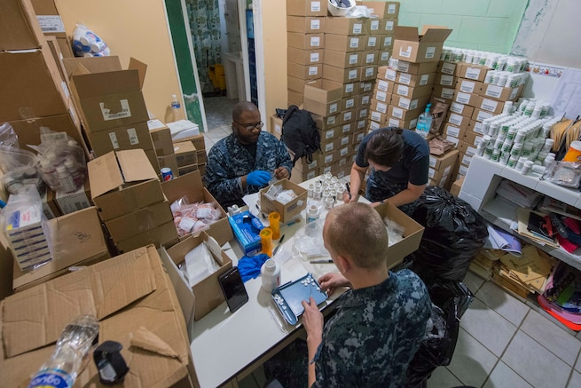 Sailors organize medical prescriptions at a table.