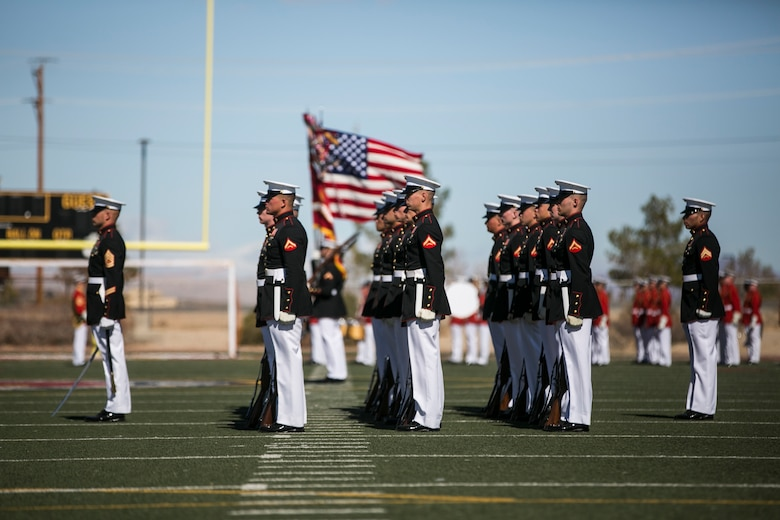 The U.S. Marine Corps Silent Drill Platoon, Battle Colors Detachment, Marine Barracks Washington, D.C., stands in formation as the colors are presented during the Battle Colors Ceremony at Felix Field aboard Marine Corps Air Ground Combat Center, Twentynine Palms, Calif., March 14, 2018. The ceremony is held to honor Marine Corps traditions through the Drum Corps, the Silent Drill Platoon and the Battle Colors Detachment. (U.S. Marine Corps photo by Lance Cpl. Margaret Gale)