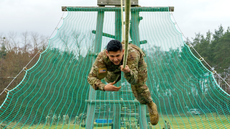 A soldier moves down a rope above a green net.